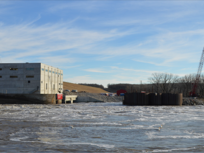 Downstream side of dam showing powerhouse and cofferdam partially removed. March 2019